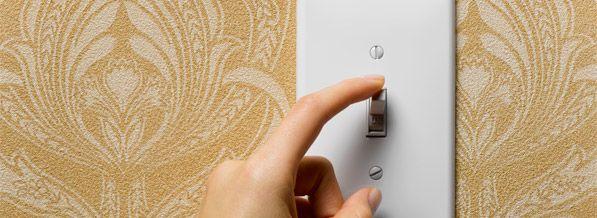 una mano va a apagar la luz mediante un interruptor